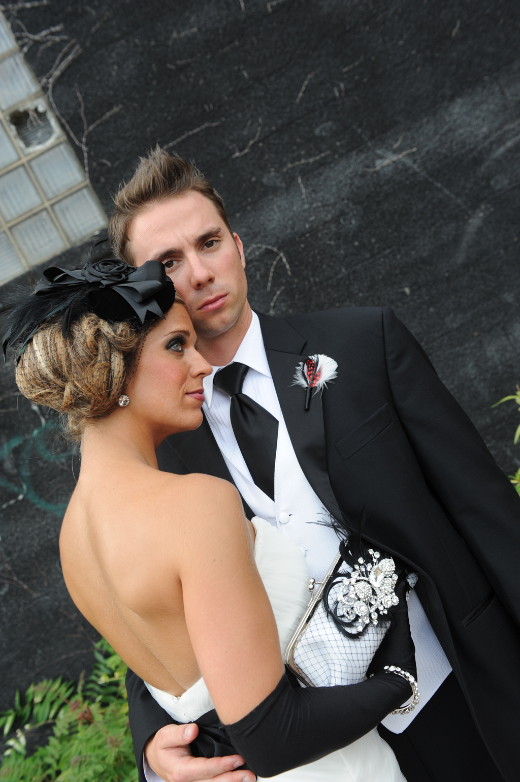 Bride and Groom. Bride carrying a handmade rhinestone and feather clutch bag by ANGEE W.